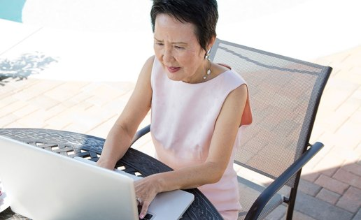 older-woman-at-laptop-outdoors
