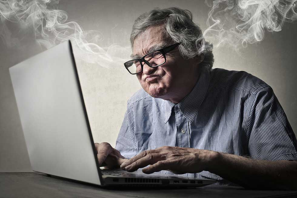 senior-using-laptop-blowing-steam